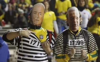 Brazil fans wear masks of FIFA president Sepp Blatter (L) and former Brazilian Soccer Confederation president Jose Maria Marin as they await the start of their team