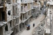 Residents walk near damaged buildings in the anti-government held area of Old Aleppo, Syria.