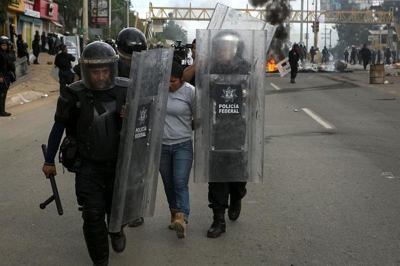 Federal Police detain a protester following battles to clear blockades on the highways surrounding Oaxaca City.