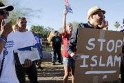 "A demonstrator shouts and carries a ""Stop Islam"" sign outside the Islamic Community Center of Phoenix, Arizona on May 29, 2015."
