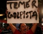 Protester holds sign accusing Temer of being a coup-plotter.