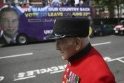 A Chelsea Pensioner passes in front of the UK Independence Party (UKIP) pro-brexit campaign bus, parked in front of the Chelsea Flower Show in London