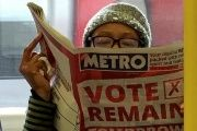 A woman reads a newspaper on the underground in London with a