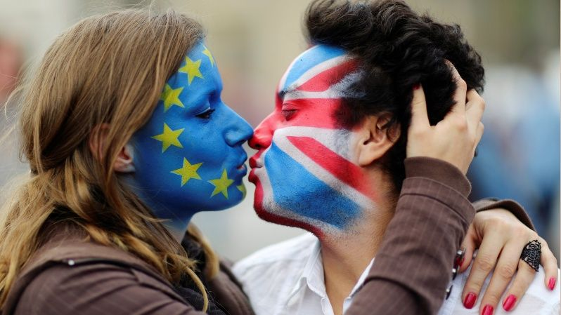 Two activists with the EU flag and Union Jack painted on their faces kiss each other in front of Brandenburg Gate to protest against Brexit in Berlin.