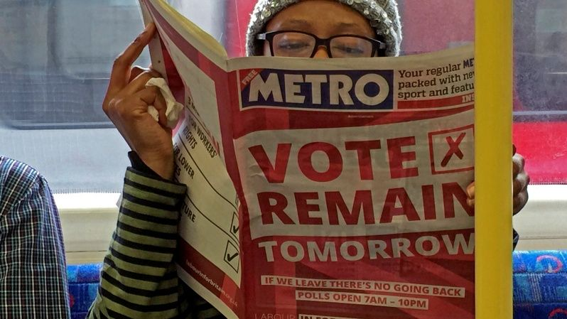 "A woman reads a newspaper on the underground in London with a ""vote remain"" advert for the Brexit referendum."