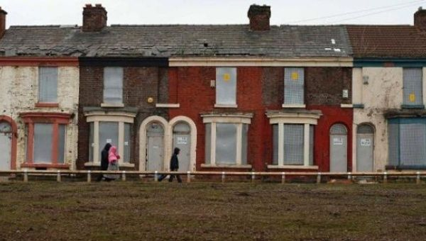 People walk past a row of boarded up terraced houses in Liverpool in 2013.