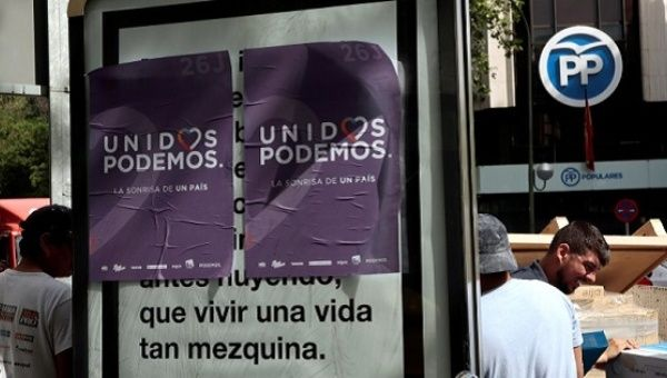 Unidos Podemos posters pasted on a street sign.