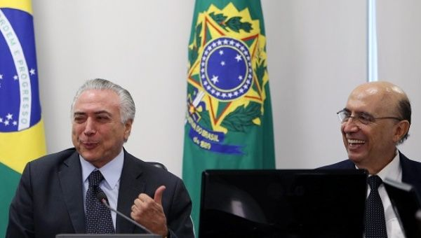 Michel Temer gestures to Finance Minister Meirelles at the Planalto Palace in Brasilia