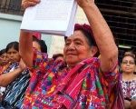An Indigenous women holds up the case presented to the court for intellectual property rights over Mayan textiles.