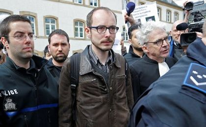 Former PricewaterhouseCoopers employee Antoine Deltour (C) and his lawyer William Bourdon (R) are escorted by police as they leave the court after the first day of the LuxLeaks trial in Luxembourg, April 26, 2016.