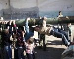 Children hang from the barrel of a tank, which was captured by the Free Syrian Army, in Azaz city, north Aleppo, Syria.