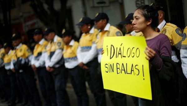 "An activist holds a sign that reads ""Dialogue without bullets"" in Mexico City."