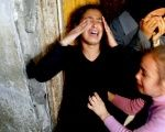 Two girls cry after their sister Mamdoh Abaid was killed in an Israeli airstrike.