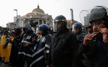 Riot police stand guard outside the Bellas Artes theatre as people from the CNTE teachers' union take part in a march against President Enrique Pena Nieto