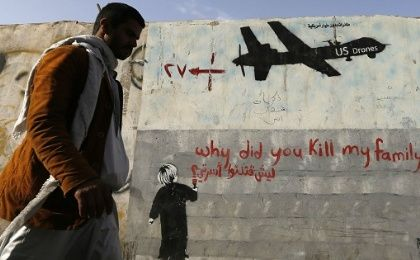 A man walks past a graffiti denouncing strikes by US drones in Yemen.