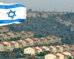 An Israeli flag flutters over the view of the illegal West Bank settlement of Ofra.