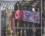 African migrants gesture behind a fence inside Holot, Israel's new Negev desert detention center.