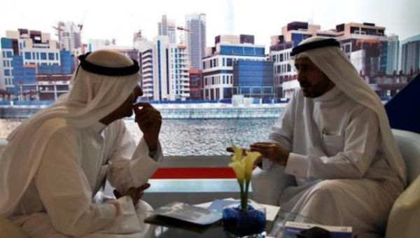 Businessmen speak to each other during the Cityscape real estate exhibition in Dubai, Oct. 2, 2012.