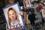 People hold signs calling for the release of imprisoned wikileaks whistleblower Chelsea Manning while marching in a gay pride parade in San Francisco, California.
