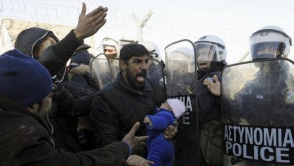 A stranded migrant holding a baby shouts next to a Greek police cordon following scuffles at the Greek-Macedonian border, near the village of Idomeni.