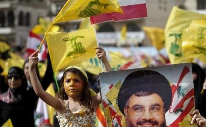 A girl carries Hezbollah and Lebanese flags while Hezbollah leader Sayyed Hassan Nasrallah talks at a festival celebrating Resistance and Liberation Day.
