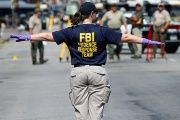 A member of the FBI Evidence Response Team stands on Elm Street outside El Centro College in Dallas, Texas.