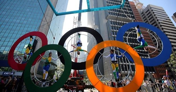 Acrobats perform on the Olympics rings at Paulista Avenue in Sao Paulo
