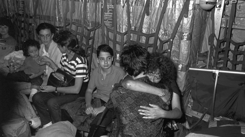 Journalist Maruja Torres hugs a photographer inside a plane returning the body of the reporter Juan Antonio Rodriguez, killed during the U.S. invasion of Panama.