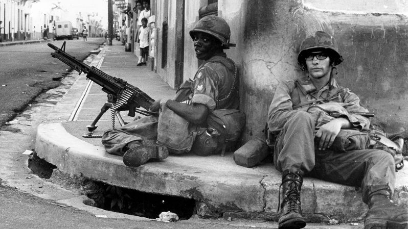 Two U.S. soldiers guard a street intersection during the invasion of the Dominican Republic.