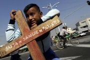 A migrant from Guatemala holds a cross during a human rights protest amid a crackdown on Central American citizens crossing overland toward the U.S.