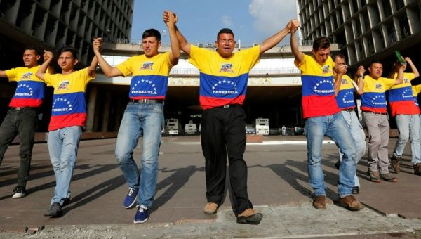 Christian believers gesture as they chant and pray close to the National Electoral Council (CNE) headquarters in Caracas, Venezuela July 26, 2016.