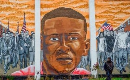 A man walks past a mural of Freddie Gray in the Sandtown-Winchester neighborhood of Baltimore, Maryland, U.S. on Dec. 17, 2015.