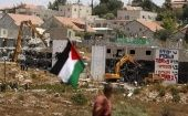 A Palestinian flag as Israeli heavy machinery demolish apartment blocs in the West Bank Jewish settlement of Beit El July 29, 2015