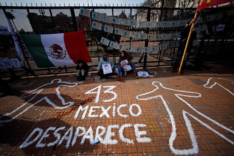 "Demonstrators sit next to a graffiti that reads ""43 (for the missing students of Ayotzinapa College) - Mexico disappears"" outside the Casa Rosada Presidential Palace during a protest against the visit to Argentina by Mexico"