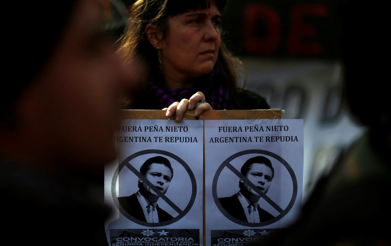 A woman holds up a sign with portraits of Mexico