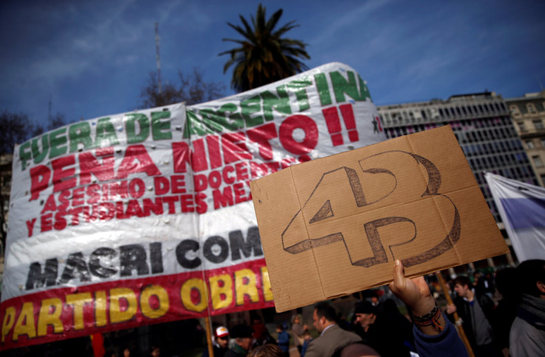 "A man holds up a sign that reads ""43 (for the 43 missing students of Ayotzinapa College) outside the Casa Rosada Presidential Palace during a protest against the visit to Argentina by Mexico"
