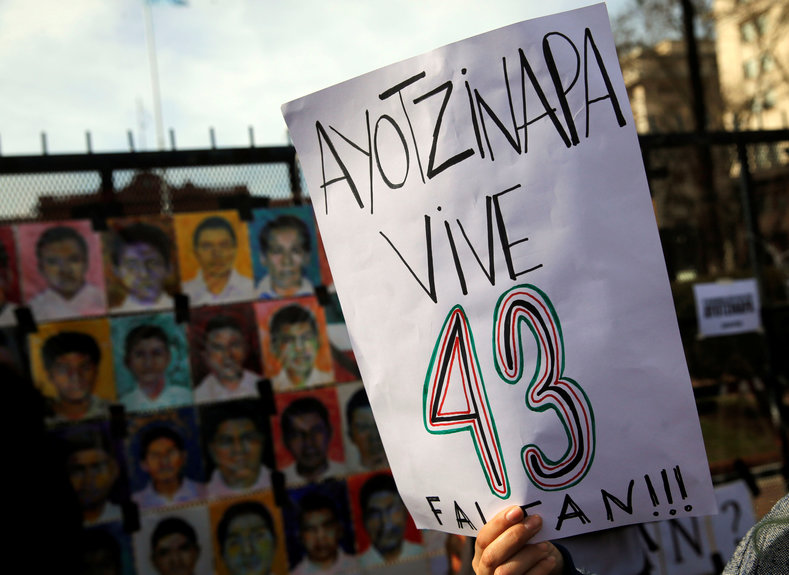"A woman holds up a sign that reads ""Ayotzinapa lives - 43 are missing"" next to pictures of the 43 missing students of Ayotzinapa College on a police fence outside the Casa Rosada Presidential Palace during a protest against the visit to Argentina by Mexico"