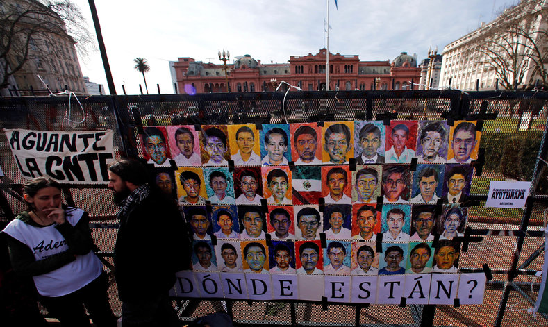 Demonstrators stand next to pictures of the 43 missing students of Ayotzinapa College on a police fence outside the Casa Rosada Presidential Palace during a protest against the visit to Argentina by Mexico