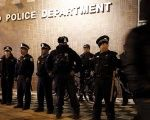 A file photo shows a protester walking past a line of police officers standing guard in front of the District 1 police headquarters in Chicago, Illinois November 24, 2015.