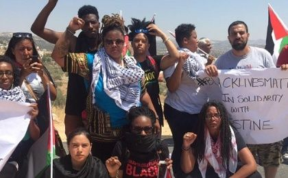 Black Lives Matter activists pose for a photo with local Palestinian activists during a protest in Bilin village near Ramallah, July 29, 2016.