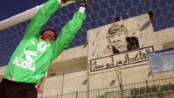 A Palestinian goalkeeper practices fielding shots in a file photo at the Gaza soccer stadium where a large mural of Palestinian President Yasser Arafat hangs behind the goal.