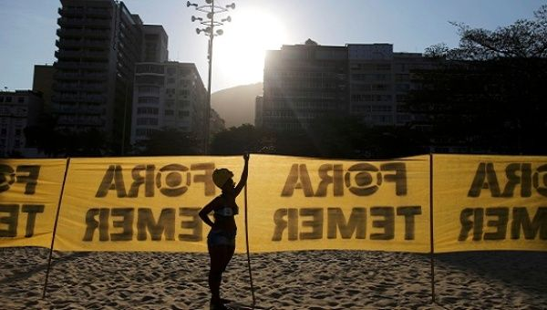 "A person stands in front of a banner which reads ""Temer out"" on Copacabana before the opening ceremony of the Rio 2016 Olympic Games in Rio de Janeiro, August 5, 2016."