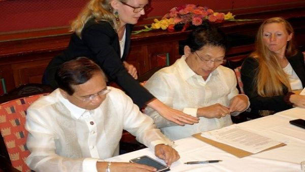 Philippine government negotiators Jesus Dureza (L) and Silvestre Bello sign an indefinite ceasefire agreement with communist rebels at a meeting in Oslo, Norway, August 26, 2016.