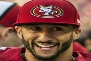 U.S. football player Colin Kaepernick sits during the U.S. National Anthem to protest oppression