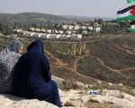 Palestinians look at the Jewish Hallamish settlement in the West Bank village of Nabi Saleh.