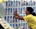A woman cries in front of photographs of disappeared family members in Medellin, Colombia, March 15, 2013.
