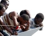 Migrants wait to disembark from the Italian Navy vessel Sfinge in the Sicilian harbour of Pozzallo, southern Italy, Aug. 31, 2016.