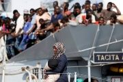A woman disembarks from the Italian Navy vessel Sfinge in the Sicilian harbor of Pozzallo, southern Italy, Aug. 31, 2016.