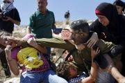 Palestinian protesters struggle with an Israeli soldier to prevent the arrest of a boy for throwing rocks.