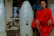 A Buddhist monk poses next to unexploded bombs dropped by the U.S. Air Force planes during the Vietnam War, in Xieng Khouang in Laos Sept. 3, 2016.